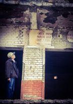 Ambassador Arvizu reads the remains of a Communist slogan at the cell blocks in Spaç. | Ambasadori Arvizu lexon mbetjet e një parullë komuniste në Spaçit.